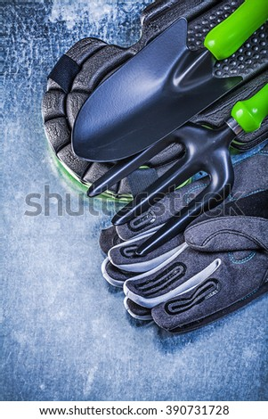 Gardening safety gloves knee protectors hand shovel trowel fork on metallic background agriculture concept. - stock photo