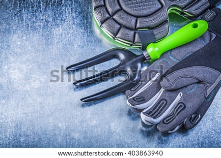 Gardening safety gloves knee protectors trowel fork on metallic background agriculture concept. - stock photo