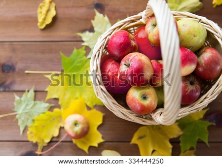 gardening, season, autumn and fruits concept - close up of wicker basket with ripe red apples and leaves on wooden table - stock photo