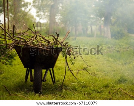 Gardening season - green lawn with wheelbarrow - stock photo