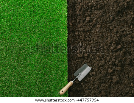 Gardening shovel on the fertile soil and grass, gardening and landscaping concept - stock photo