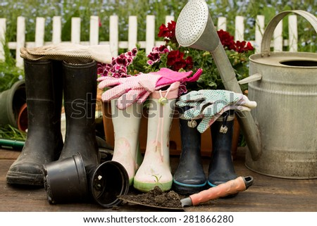 gardening tools, adult and child boots and handshoes in the garden  - stock photo