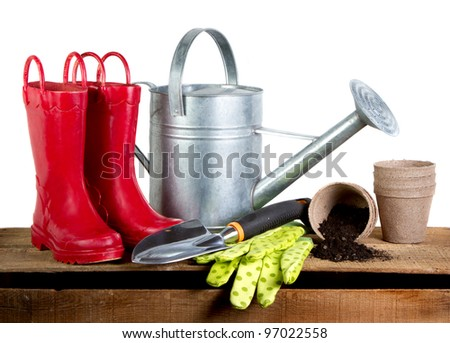 Gardening tools and red rubber boots isolated on a white background - stock photo