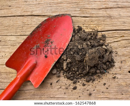 gardening tools and soil on a wood background - stock photo