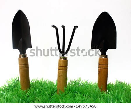 Gardening tools on grass on white background - stock photo