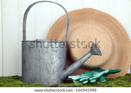 Gardening tools on grass on wooden background
