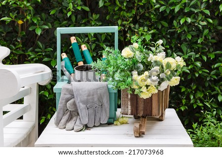 Gardening tools on wooden table in garden - stock photo