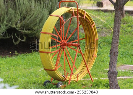 Gardening water hose on the spool. Yellow hose on grass. - stock photo
