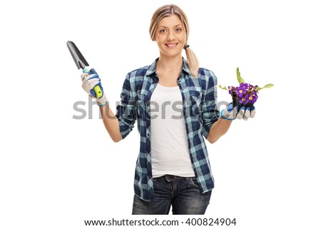 Gardening woman holding a spade and a flower in a pot isolated on white background - stock photo