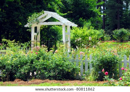Gardens of the American Rose Center in Shreveport, Louisiana has beautiful landscaping with this white wooden pavillion and white picket fence.  Hollyhocks and roses bloom together around fence. - stock photo