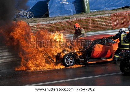 GARDERMOEN RACEWAY, NORWAY - MAY 14: Fire fighters arrive after race car explodes into flames during a drag race on May 14,2011 at Gardermoen Raceway, Norway. - stock photo
