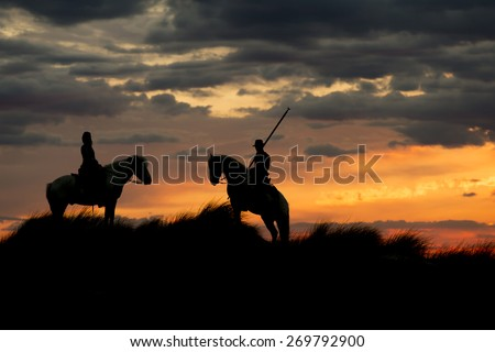 Gardians silhouetted on White horses of Camargue France at sunrise - stock photo