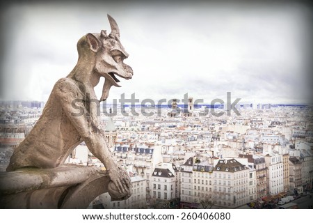 Gargoyle (chimera), famous stone demons, with Paris city on background. View from the tower of the Notre Dame de Paris cathedral. France. Travel, architecture concept. Copy space. Place for your text.