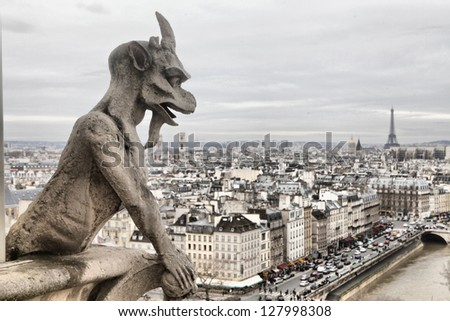 Gargoyle (chimera) on Notre Dame de Paris close up against a moody sky, HDR - stock photo
