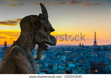 Gargoyle looking at the eiffel tower at dusk