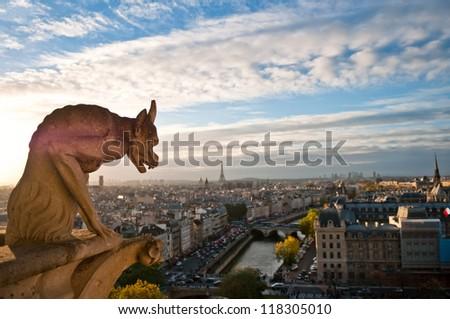 Gargoyle overlooking Paris up on Notre Dame de Paris - stock photo