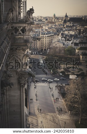 Gargoyle overlooking Paris up on Notre Dame de Paris - stock photo