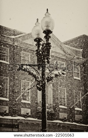 garland and holiday lights deorate this old cast iron victorian  street lamp during a snow storm in harvard square cambridge massachusets