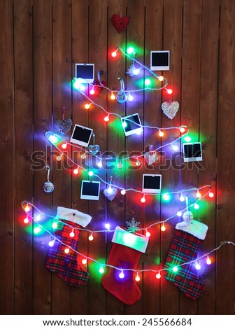 Garland in shape of Christmas tree on wooden wall background - stock photo