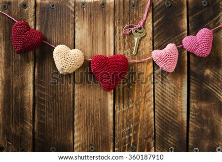 Garland knitting hearts and key on old wooden panel. Background Valentines Day.Valentines day cards. - stock photo