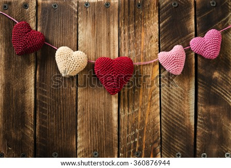 Garland knitting hearts on old wooden panel. Background Valentines Day.Valentines day cards.