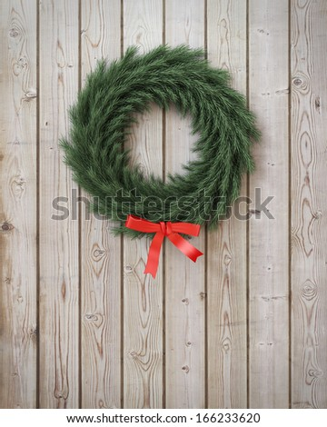 garland wreath with red ribbon on vintage wooden planks wall - stock photo
