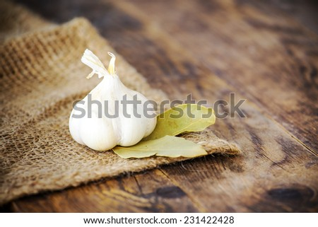 Garlic and bay leaves on the table. - stock photo