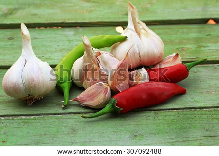 garlic and hot peppers on old wooden background - stock photo