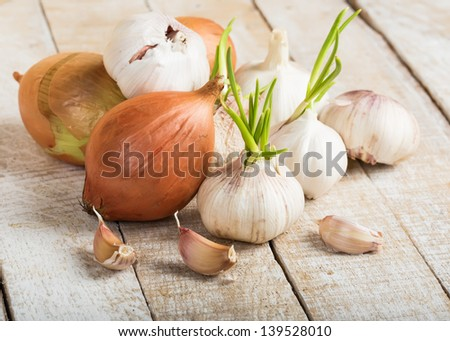 Garlic and onion on wooden background. Selective focus. - stock photo