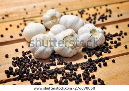 Garlic and pepper on a wooden background - stock photo
