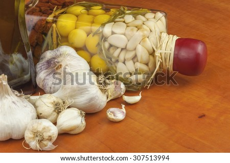 Garlic, aromatic ingredients for flavoring food. Home remedy for colds and flu. Garlic marinated in olive oil. Seasoning food. Preparing for the garden party and barbecue meat - stock photo