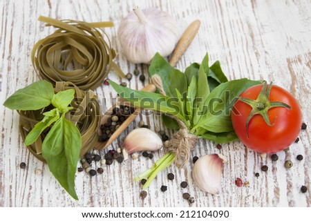 Garlic, basil, peppers and tagliatelle  on a wooden background