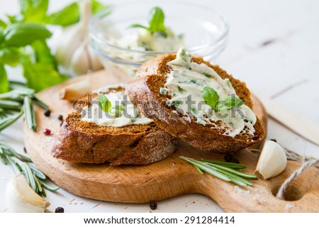 Garlic bread - baguette slices, garlic butter, herbs, wood board, white wood background - stock photo