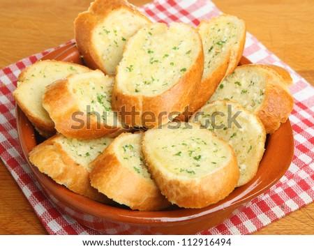 Garlic bread in terracotta dish - stock photo