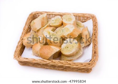 Garlic bread in wicker basket isolated against white background. - stock photo