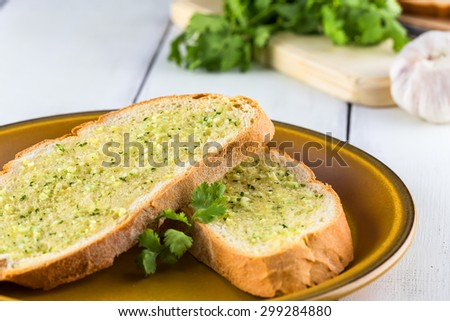 Garlic bread with parsley on rustic white table - stock photo