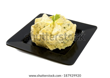 Garlic butter on a black plate isolated over white - stock photo