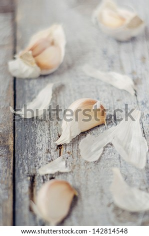 Garlic cloves on a rustic wooden table - stock photo