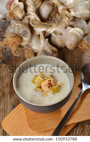 Garlic cream soup with croutons and almonds - stock photo