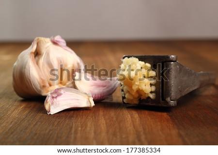 Garlic crushed and garlic press - stock photo