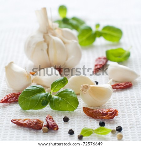 Garlic, dried chili pepper, black pepper and basil on kitchen towel