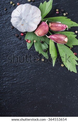 Garlic. Fresh Garlic. Cloves of garlic with parsley herb top leaves and pepper four colours. - stock photo