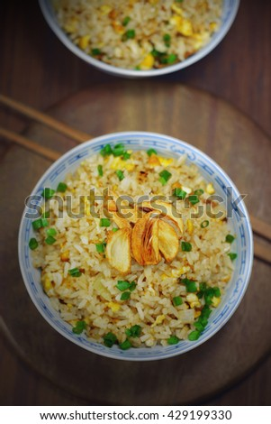 garlic fried rice with egg and fried garlic on top. homemade chinese cuisine. low light picture.
