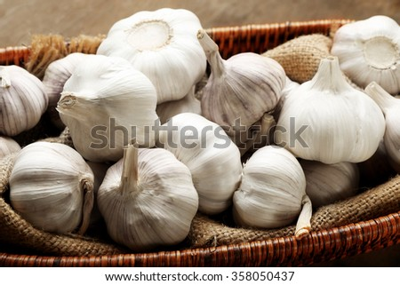 Garlic in wicker bowl on wooden background, close up