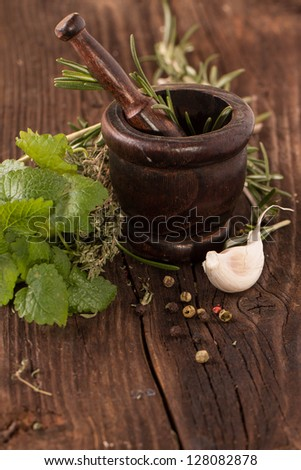 garlic, mint and rosemary in wooden vintage mortar on old wooden table - stock photo