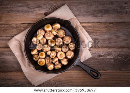 Garlic mushrooms cooked in a cast iron skillet, resting on greaseproof paper on old table. Overhead view with retro style processing.