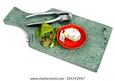 Garlic on a red stone plate and a garlic press with some lettuce leaves on a green marble cutting board