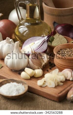 Garlic, onion, coriander, sesame seeds, black pepper, bay leaf, sea salt, olive oil - stock photo