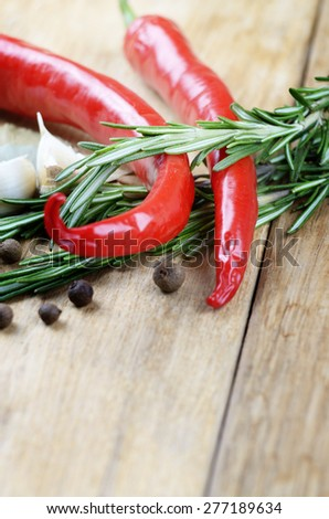 Garlic, rosemary and chili pepper on wooden table with copy space - stock photo