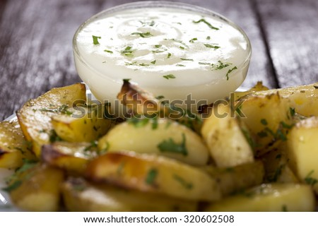 Garlic sauce in bowl and some backed potatoes out of focus - stock photo